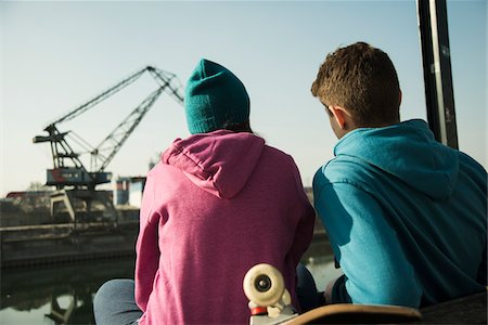 Backview of teenage girl and boy sitting on bench outdoors with skateboard, industrial area, Mannheim, Germany Stock Photo - Premium Royalty-Free, Code: 600-07584763