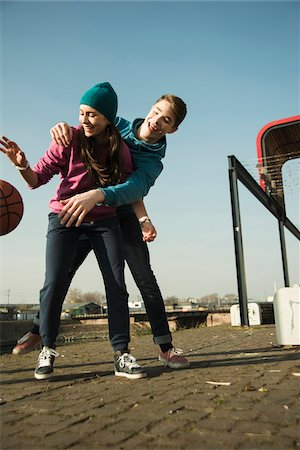 Teenage boy and girl playing basketball outdoors, industrial area, Mannheilm, Germany Stock Photo - Premium Royalty-Free, Code: 600-07584774