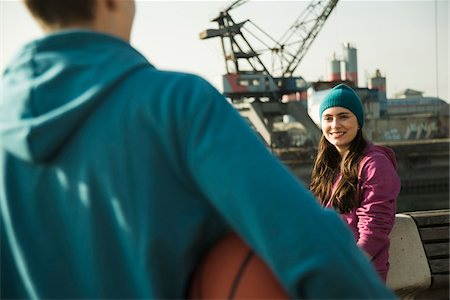 Teenage girl outdoors wearing toque, smiling and looking at teenage boy holding basketball, industrial area, Mannheim, Germany Stock Photo - Premium Royalty-Free, Code: 600-07584781