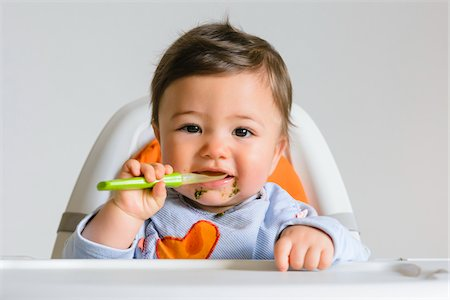 Baby Boy Eating with Spoon in High Chair, Studio Shot Stock Photo - Premium Royalty-Free, Code: 600-07596018