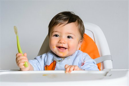 Baby Boy Eating with Spoon in High Chair, Studio Shot Stock Photo - Premium Royalty-Free, Code: 600-07596020