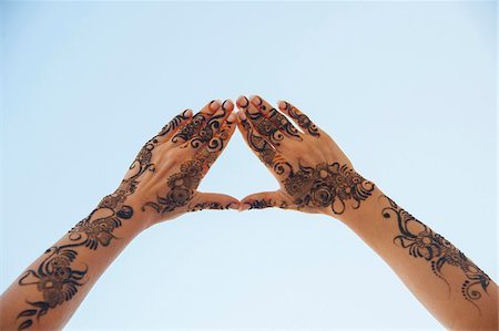 Woman's Hands and Arms Painted with Henna in Arabic Style, forming Triangle with Fingers against Blue Sky, Muscat, Oman Stock Photo - Premium Royalty-Free, Code: 600-07591301