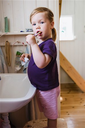 2 year old girl brushing her teeth at the sink in the bathroom looking at camera, Sweden Stock Photo - Premium Royalty-Free, Code: 600-07734372
