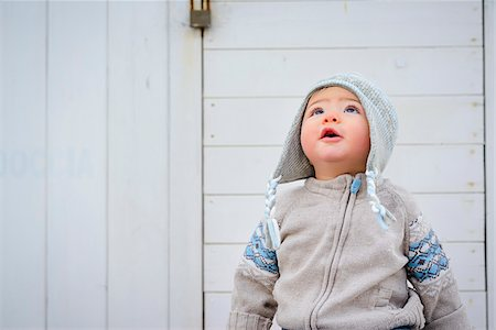 fashion - Close-up of seven month old baby boy wearing sweater and hat outdoors in winter at seaside, looking upwards Stock Photo - Premium Royalty-Free, Code: 600-07734410
