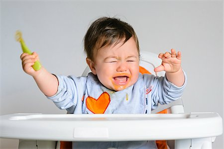 Close-up of eight month old baby boy sitting in highchair, holding spoon and crying Stock Photo - Premium Royalty-Free, Code: 600-07734413