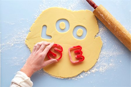 Overhead View of Woman's Hand using Cookie Cutters to spell LOOSE in Rolled out Suger Cookie Dough, Studio Shot Stock Photo - Premium Royalty-Free, Code: 600-07784428