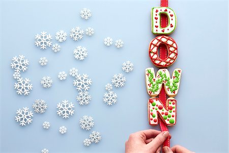 snowflakes  holiday - Overhead View of Decorated Christmas Cookies spelling DOWN on Blue Background with Snowflakes Stock Photo - Premium Royalty-Free, Code: 600-07784423