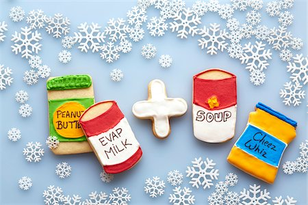 Overhead View of Sugar Cookies Decorated like Food Products on Blue Background with Snowflakes Stock Photo - Premium Royalty-Free, Code: 600-07784433