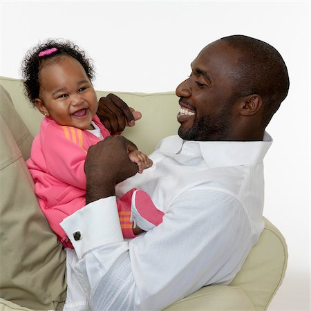 Portrait of Father and Baby Girl on Chair, Studio Shot Stock Photo - Premium Royalty-Free, Code: 600-07784456