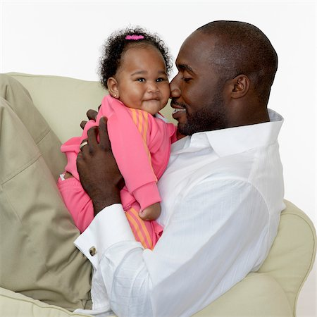 Portrait of Father and Baby Girl on Chair, Studio Shot Stock Photo - Premium Royalty-Free, Code: 600-07784457