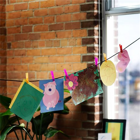 Children's Artwork Hanging on Clothesline by Window Stock Photo - Premium Royalty-Free, Code: 600-07784460