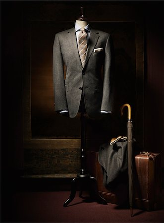Suit jacket, shirt and tie displayed on dress form with suitcase, coat, gloves and an umbrella beside on floor, studio shot Stock Photo - Premium Royalty-Free, Code: 600-07783900