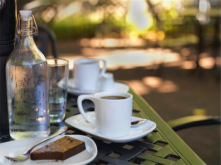 seasonal - Coffee in white cups and saucers, water bottle and glass with chocolate brownie on plate at outdoor patio, Canada Stock Photo - Premium Royalty-Free, Code: 600-07803118
