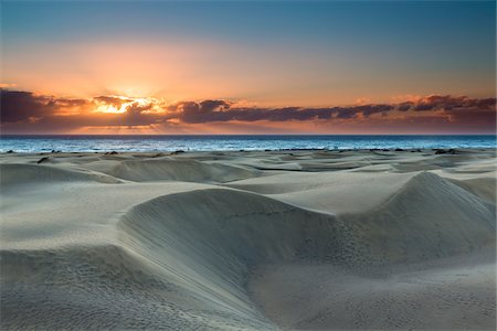 Dunes of Maspalomas at sunrise, with the Atlantic ocean in the distance, San Bartolome de Tirajana, Gran Canaria, Las Palmas, Canary Islands Stock Photo - Premium Royalty-Free, Code: 600-07849603