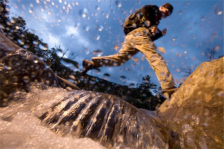 Low angle view of man jumping over a stream while hiking in New Hampshire, USA Stock Photo - Premium Royalty-Free, Code: 600-07945090