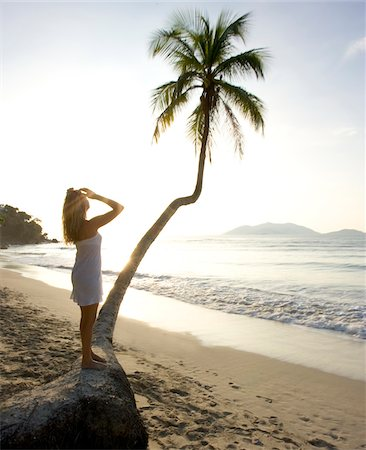 Woman standing on palm tree on beach with sun, Cane Garden Bay, Tortola, Caribbean Stock Photo - Premium Royalty-Free, Code: 600-07945128
