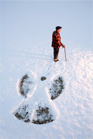 An elderly using a cane, standing in the snow beside a snow angel, New England, USA Stock Photo - Premium Royalty-Free, Code: 600-07945121