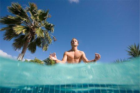 sitting under tree - Man doing yoga poolside, Antigua, Caribbean Stock Photo - Premium Royalty-Free, Code: 600-07945144