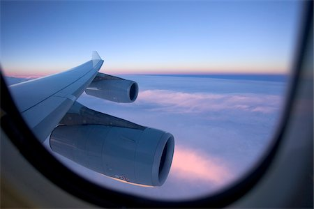 An aircraft wing and engines as seen from the window of a jet while flying above the clouds at sunset. Stock Photo - Premium Royalty-Free, Code: 600-07945140