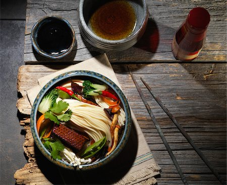 Noodle Soup with Bok Choy, Cilantro, Enoki Mushrooms, Tofu, Snow Peas, Red Chili Peppers, Soy Sauce and Sesame Oil with Chop Sticks on Wooden Table, Studio Shot Stock Photo - Premium Royalty-Free, Code: 600-07945374