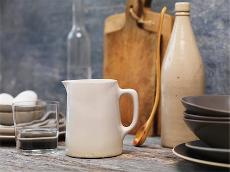 Still life of water jug, with glass of water, wooden spoon, cutting boards, eggs and grey plates. Stock Photo - Premium Royalty-Free, Code: 600-07965938