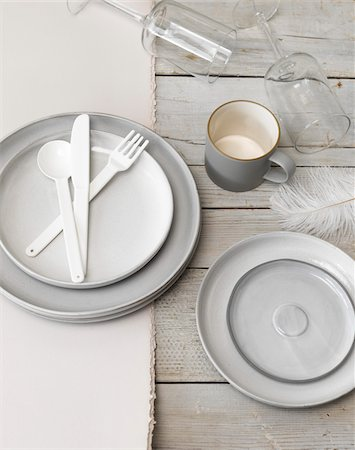 Still life of place setting with plates, cutlery, mug, wine glasses and feather. Stock Photo - Premium Royalty-Free, Code: 600-07965942