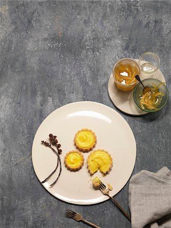slate - Overhead View of Lemon Tarts on White Plate with Candied Lemons, Studio Shot Stock Photo - Premium Royalty-Free, Code: 600-07966140