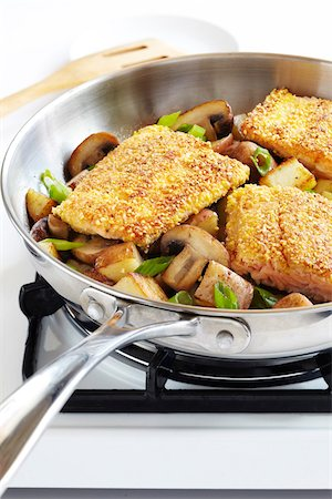 stove - Cornmeal crusted trout fillets in a skillet with potatoes, mushrooms and green onions on a gas stove, studio shot Stock Photo - Premium Royalty-Free, Code: 600-08002099