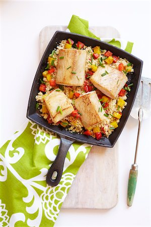 Mahi-Mahi on couscous in a cast-iron skillet with a green patterned napkin, studio shot on white background Stock Photo - Premium Royalty-Free, Code: 600-08002100