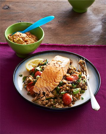 Baked Salmon with grain side dish with fork on plate and bowl of dipping sauce, studio shot Stock Photo - Premium Royalty-Free, Code: 600-08002161