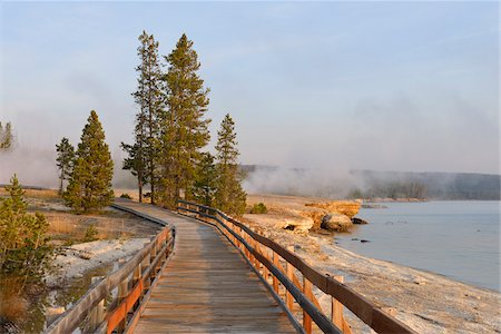 Boardwalk at West Thumb Geyser Basin with Steam from Hot Springs and Yellowstone Lake in the background, Yellowstone National Park, Wyoming, USA Stock Photo - Premium Royalty-Free, Code: 600-08002203