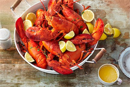 Pot Full of Cooked Whole Lobster with Sliced Lemon and Melted Butter on Wooden Tabletop Stock Photo - Premium Royalty-Free, Code: 600-08002396