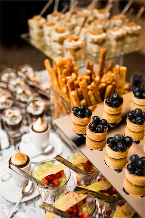 presentation (displaying) - Close-up of dessert table with a variety of platters, with blueberry tarts, puddings and parfaits, at an event, Canada Stock Photo - Premium Royalty-Free, Code: 600-08002535