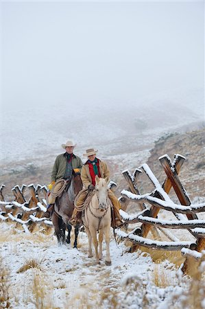 Cowboy and Cowgirl riding on horses beside fence in snow, Rocky Mountains, Wyoming, USA Stock Photo - Premium Royalty-Free, Code: 600-08026165