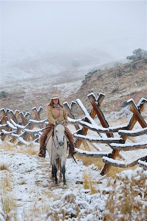 Cowgirl riding horse beside fence in snow, Rocky Mountains, Wyoming, USA Stock Photo - Premium Royalty-Free, Code: 600-08026166