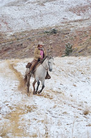 Cowgirl riding horse in snow, Rocky Mountains, Wyoming, USA Stock Photo - Premium Royalty-Free, Code: 600-08026173
