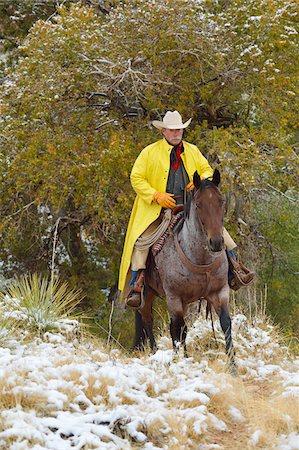 Cowboy Riding Horse in Snow, Rocky Mountains, Wyoming, USA Stock Photo - Premium Royalty-Free, Code: 600-08026184