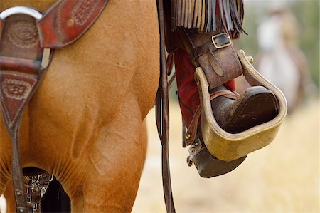 Close-up of Cowboy Riding Horse with Foot in Stirrup, Wyoming, USA Stock Photo - Premium Royalty-Free, Code: 600-08026195