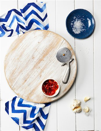 salt - Overhead View of Wooden Cutting Board with Bowl of Chili Sauce, Pizza Cutter, Garlic Cloves, Dish with Salt, and Napkin Stock Photo - Premium Royalty-Free, Code: 600-08060049