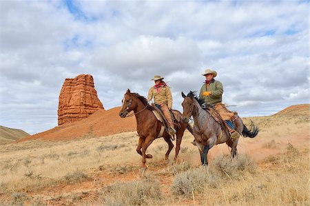 rustique - Cowboy and Cowgirl Riding Horses with Castel Rock in the background, Shell, Wyoming, USA Photographie de stock - Premium Libres de Droits, Code: 600-08082905