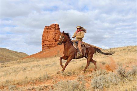 Cowgirl Riding Horse with Castel Rock in the background, Shell, Wyoming, USA Stock Photo - Premium Royalty-Free, Code: 600-08082901
