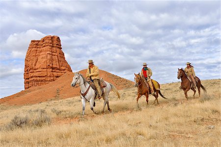 Cowboy and Cowgirls Riding Horses with Castel Rock in the background, Shell, Wyoming, USA Stock Photo - Premium Royalty-Free, Code: 600-08082918