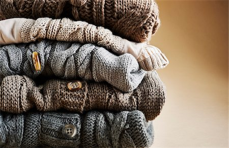 Close-up of stack of five cardigans, studio shot on brown background Stock Photo - Premium Royalty-Free, Code: 600-08107048