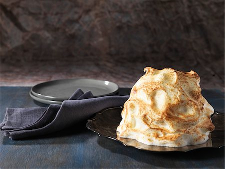 sweet   no people - Baked Alaska, golden meringue on black plate with grey napkin, studio shot on grey background Stock Photo - Premium Royalty-Free, Code: 600-08102698