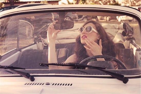 Young Woman Checking her Reflection in Rear View Mirror, Italy Stock Photo - Premium Royalty-Free, Artist: Siephoto, Image code: 600-08102809