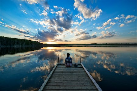 Hiker Sitting on Dock at Calm Lake at Sunset, Saskatchewan, Canada Stock Photo - Premium Royalty-Free, Code: 600-08102819