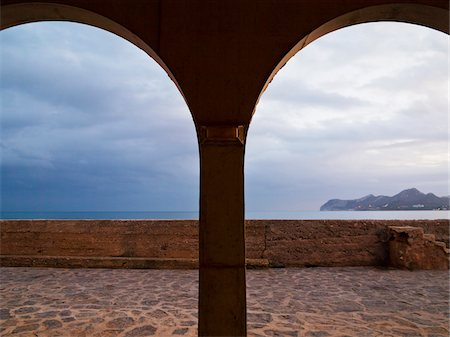 Overcast Sky through Arches at Promenade of Cala Ratjada, Majorca, Balearic Islands, Spain Stock Photo - Premium Royalty-Free, Code: 600-08102881