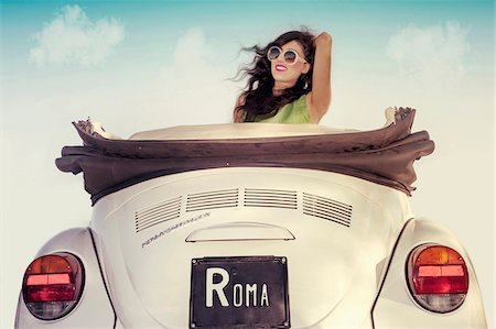 Young woman wearing sunglasses with wind in hair, sitting in a vintage, convertible Volkswagen Beetle, Italy Stock Photo - Premium Royalty-Free, Code: 600-08122180