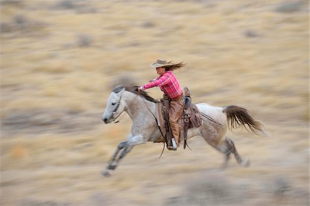 farmhand (female) - Blurred motion of cowgirl on horse galloping in wilderness, Rocky Mountains, Wyoming, USA Stock Photo - Premium Royalty-Free, Code: 600-08171776