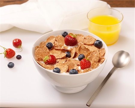 Bowl of Cereal Flakes with Berries and Orange Juice Stock Photo - Premium Royalty-Free, Code: 600-08212904